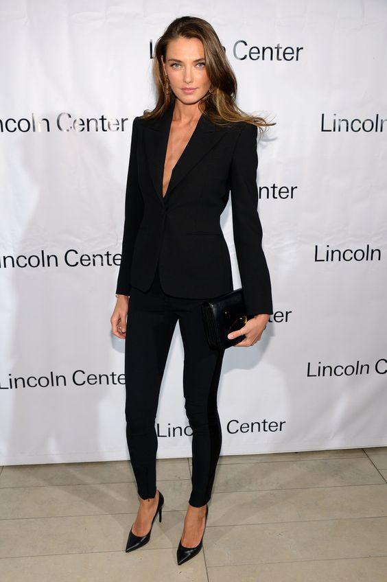 a black pantsuit with a plunging neckline and no top on, skinny pants