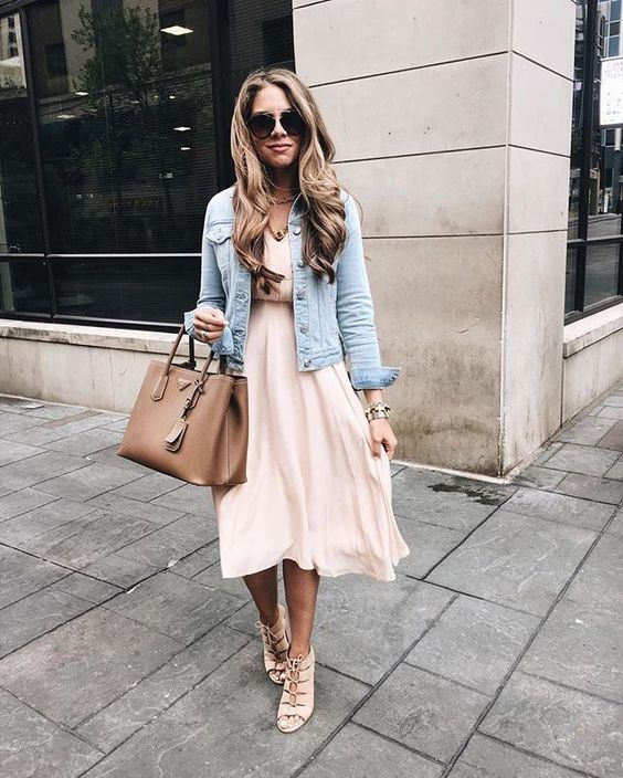 a blush midi dress, a distressed denim jacket, blush strappy shoes, a tan bag