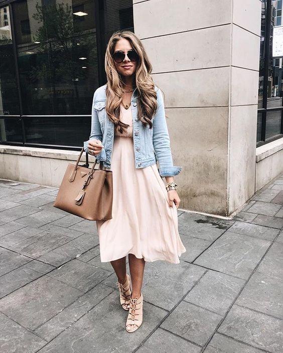 a blush midi dress, a distressed denim jacket, blush strappy shoes, a tan bag