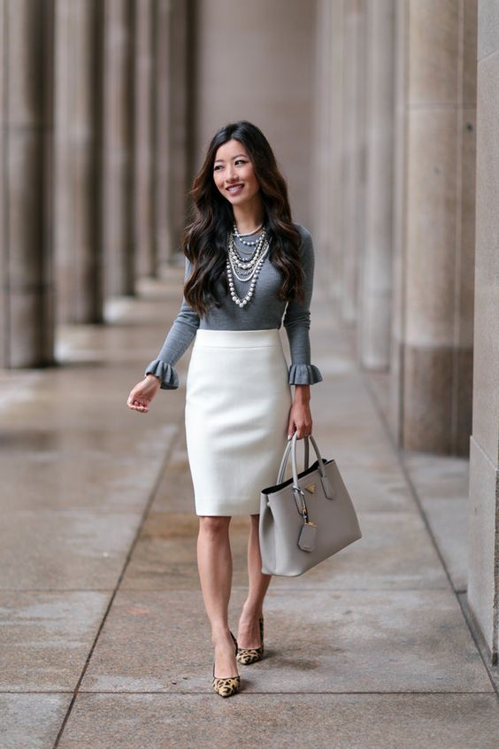 a creamy pencil skirt, a grey top with long ruffled sleeves, leopard heels, a grey bag and layered necklaces