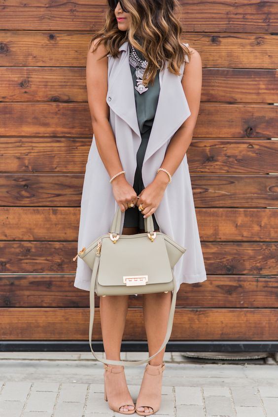 a green romper, an off-white duster vest, nude booties and a green bag for the fall