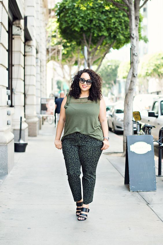 a green top, printed pants and black strappy shoes for a casual work look