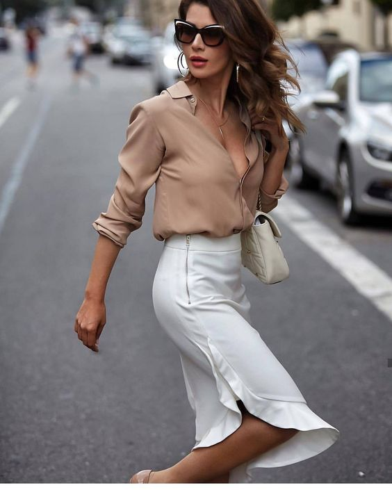 a nude silk shirt, a white midi skirt with ruffles and a creamy crossbody