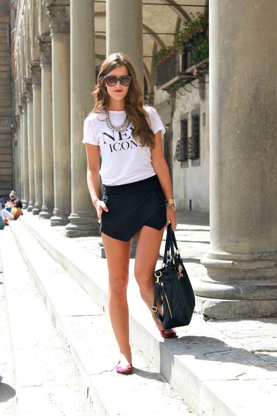 a white logo t shirt, a black asymmetrical mini skirt, red flats and a large bag