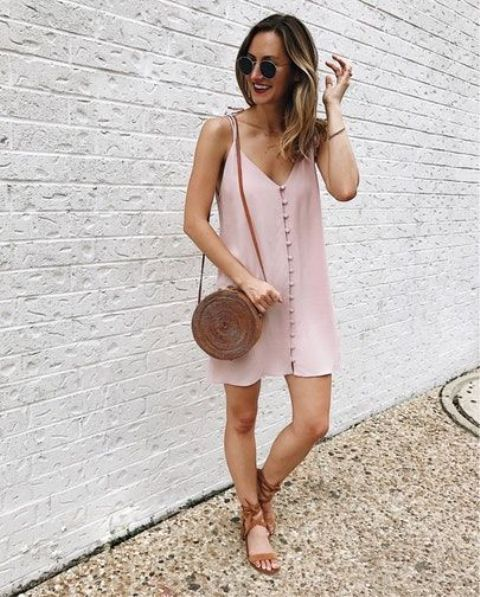 a blush slip short dress with a row of buttons, tan strappy sandals and a tan wicker bag
