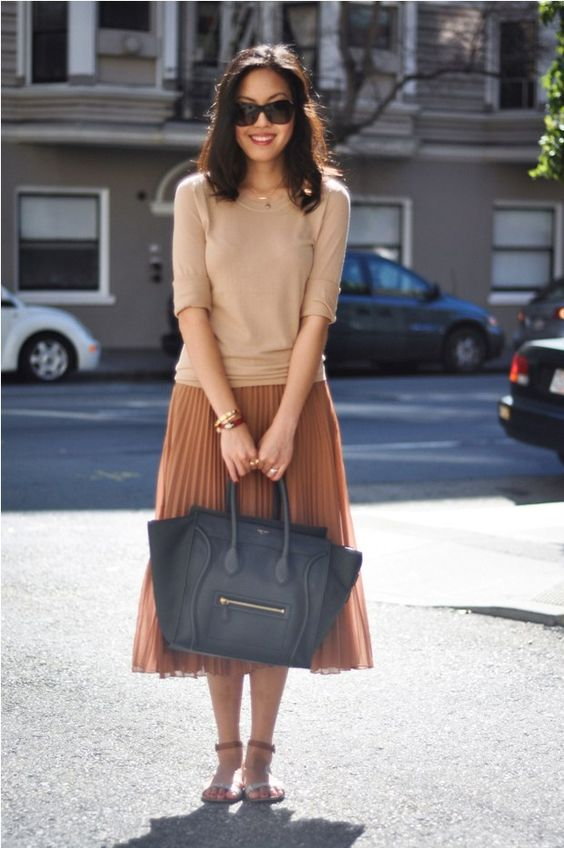 a nude top, a rust pleated midi skirt, sandals and a black bag