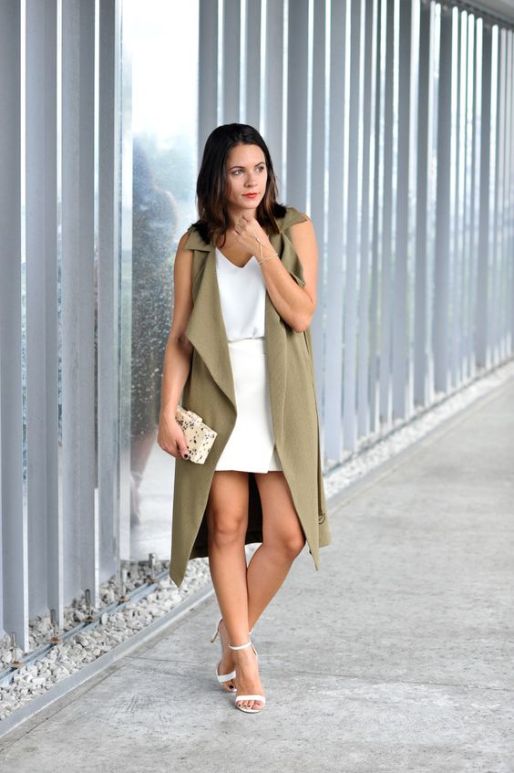 a white top, a white wrap mini skirt, white heels, a printed clutch and an olive green duster vest