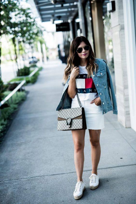 white denim shorts, a white Tommy Hilfiger tee, white sneakers, a denim jacket and a printed bag