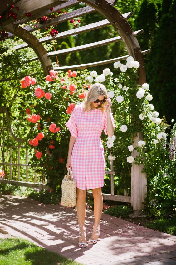 a cute pink and white plaid knee dress with short sleeves, blush lace up heels and a straw bag