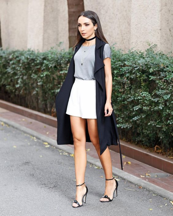 a monochromatic look with a grey tee, white shorts, a black duster vest, black heels