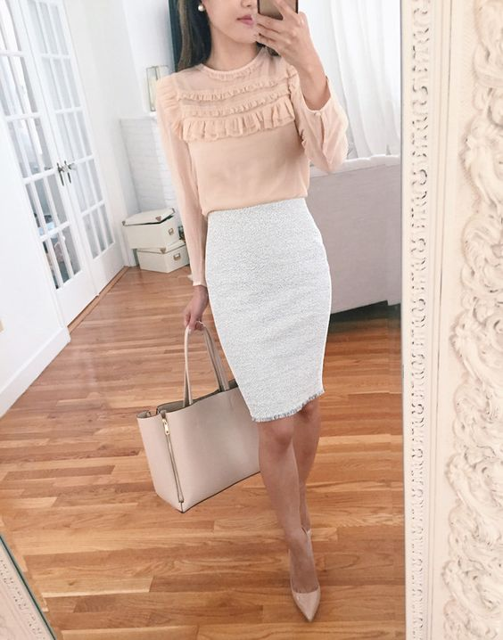 a white pencil knee skirt, a blush ruffled blouse with long sleeves, a blush bag and heels