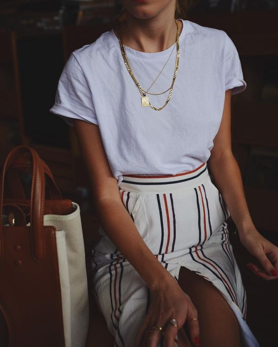 a white tee, a retro-inspired striped skirt with a front slit and layered necklaces