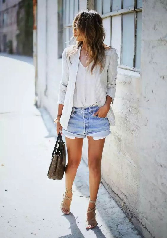 blue denim shorts, a white top, a white striped jacket, strappy sandals and a bag