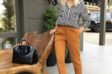 09 rust-colored cropped pants, a striped black and white shirt, platform shoes and a black bag