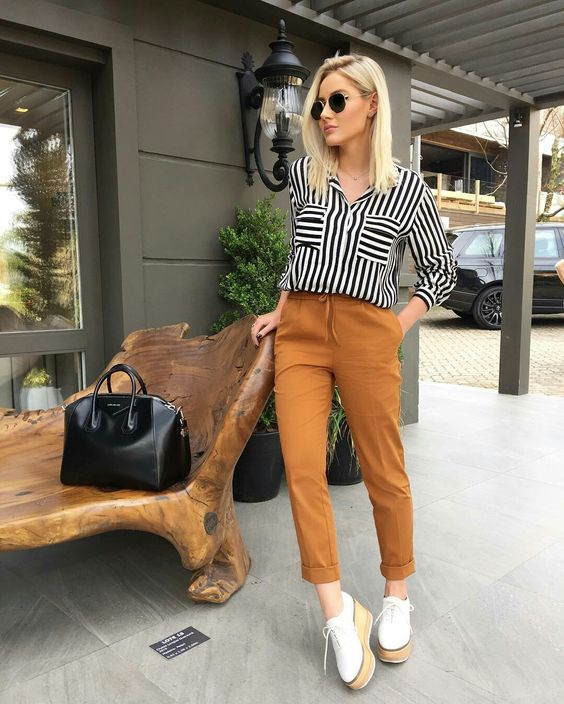 rust-colored cropped pants, a striped black and white shirt, platform shoes and a black bag
