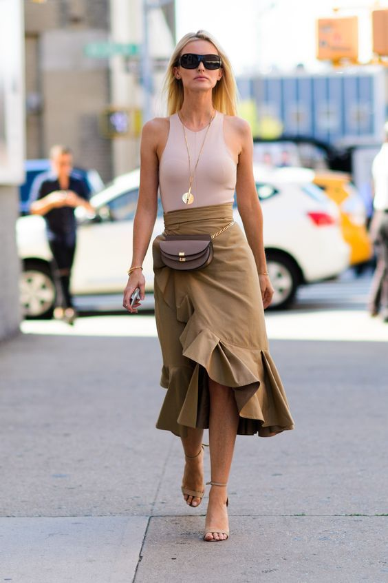 a black top, a beige ruffled asymmetrical midi skirt, nude shoes and a waist bag