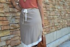 10 a coral top, a grey aymmetrical skirt, a camelbag and neutral shoes