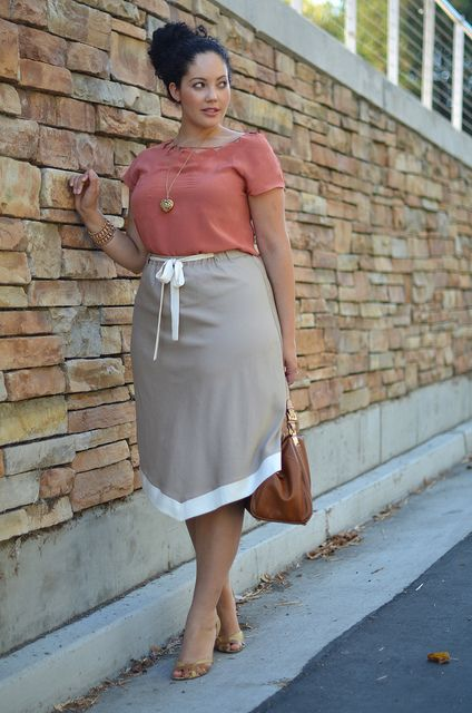 a coral top, a grey aymmetrical skirt, a camelbag and neutral shoes