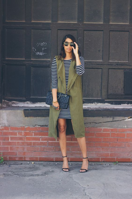 a striped bodycon over the knee dress, an olive green duster vest, black shoes and a clutch
