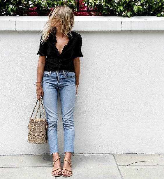 cropped blue jeans, a black shirt, nude strappy sandals and a bucket  straw bag for a relaxed look