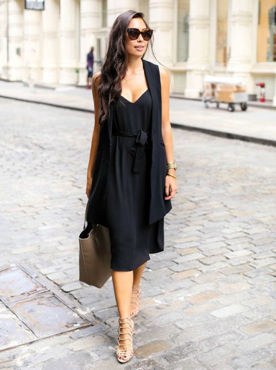 a black look with a slip dress and a duster is enlivened with blush strappy heels and a large bag