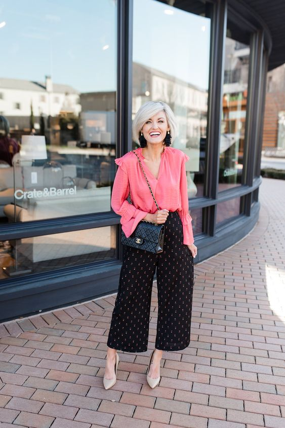 a creative work look with a pink blouse with ruffled sleeves, black printed culottes, nude shoes and trendy earrings