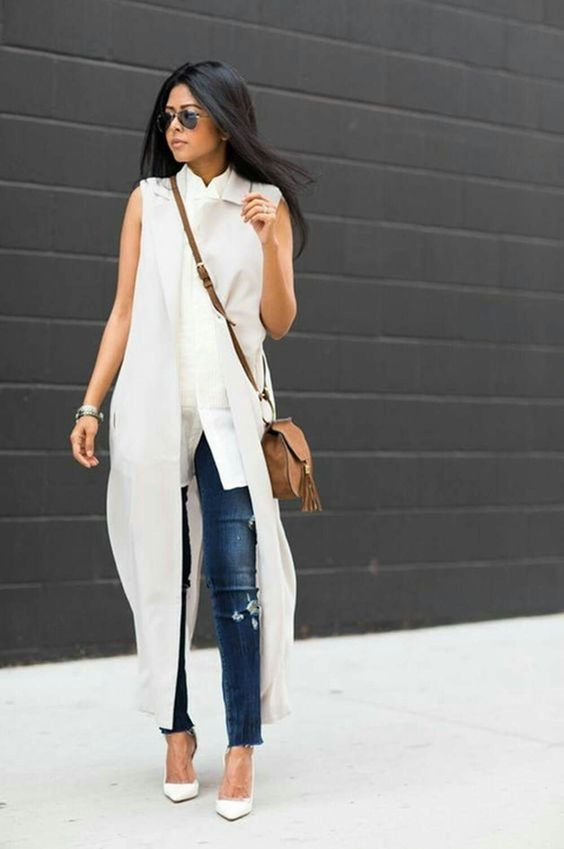 a white sleeveless top, a white duster vest, ripped blue jeans and white heels for transitional time