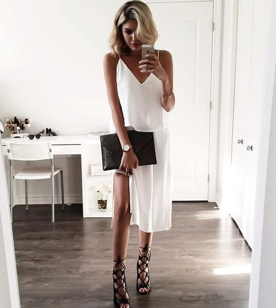 a white slip dress, black lace up shoes and a black clutch for a chic minimalist look
