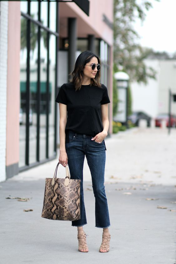 cropped navy flare jeans, a blakc tee, lace up shoes and a printed bag