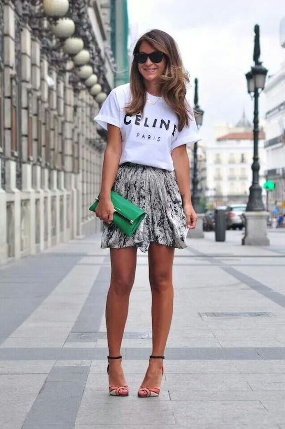 a Celine white t shirt, a graphic mini skirt, colorful shoes and a grene clutch