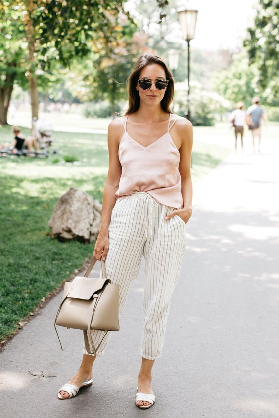 a blush spaghetti strap top, striped pants, a neutral bag