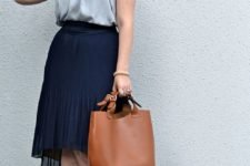 12 a grey ruffled  top, a navy high low skirt with pleats, printed shoes and a cornag bag