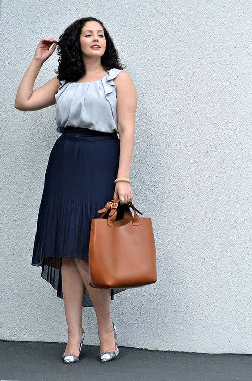 a grey ruffled  top, a navy high low skirt with pleats, printed shoes and a cornag bag