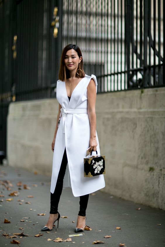 a stunning look with a black jumpsuit and a white long vest with a deep neckline plus heels