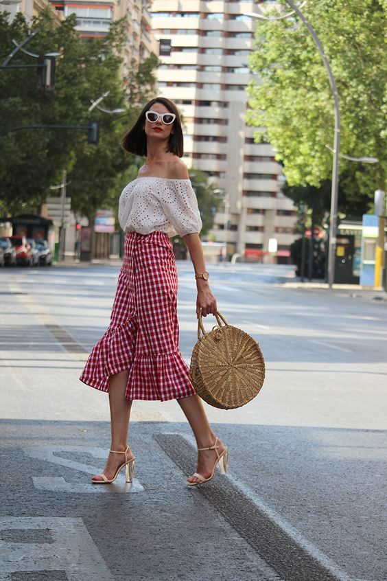 a white off the shoulder top, a red gingham midi ruffle skirt, nude shoes and a wicker bag