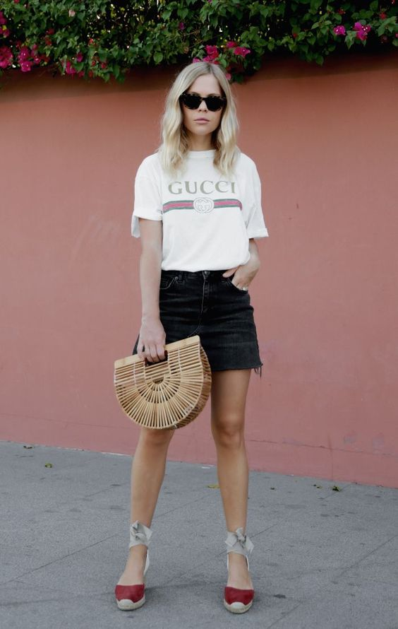 a Gucci tee, a black denim mini skirt, flats and a trendy wicker bag