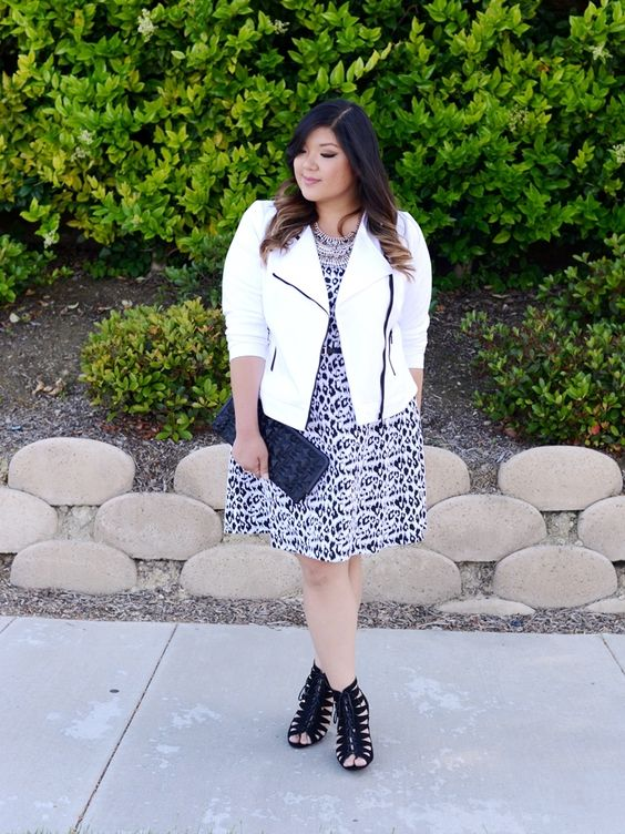 a printed knee dress, blackstrappy heels, a white biker-style jacket, a black clutch