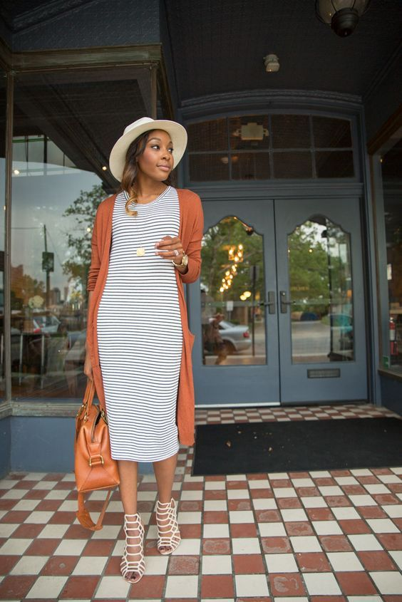 a striped bodycon midi dress, a rust long cardigan, a rust bag, a hat and white strappy heels