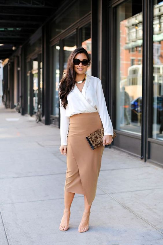 a white shirt, a tan asymmetrical midi skirt, nude shoes and a leopard print clutch