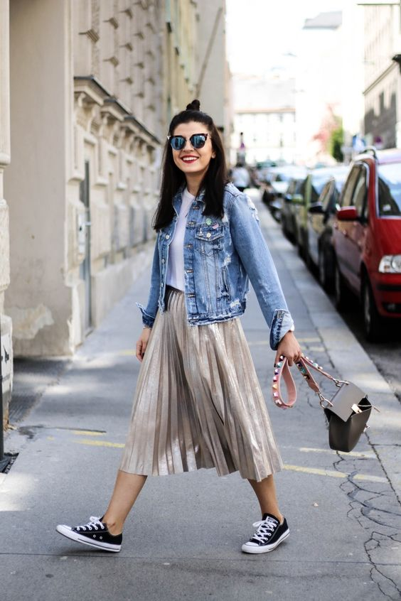 a white tee, a metallic pleated midi, black Converse and a denim jacket