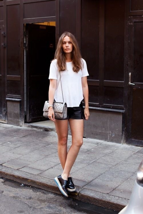 a white tee, blackleather shorts, black leather shoes and a silver  bag