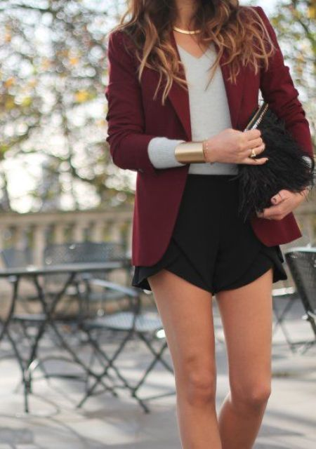 black asymmetrical shorts, a grey top and a burgundy jacket plus a fur bag for a party