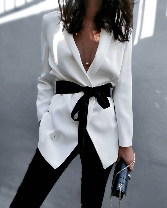 black pants, a white blouse with a blakc velvet sash and a deep neckline, which is sexy
