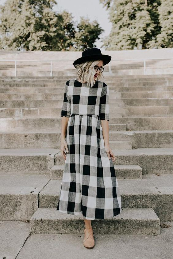 a buffalo plaid black, grey and white midi dress, tan booties and a black hat for the transition
