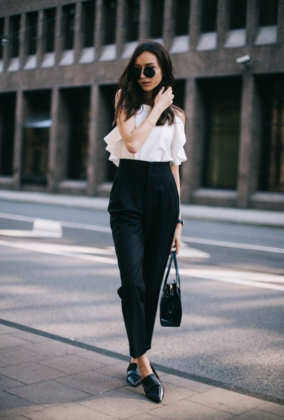a white ruffled top, black high waisted pants, black shoes and a bag for a minimalist look
