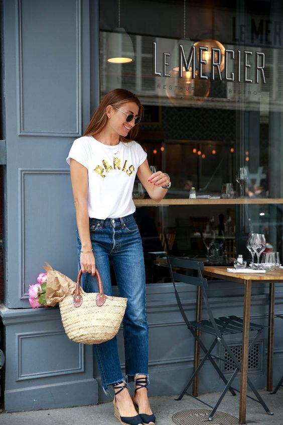 a white tee, blue raw hem jeans, strappy wedges and astraw bag