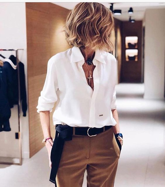camel pants, a white shirt with a deep V-neckline and a black sash on the waist