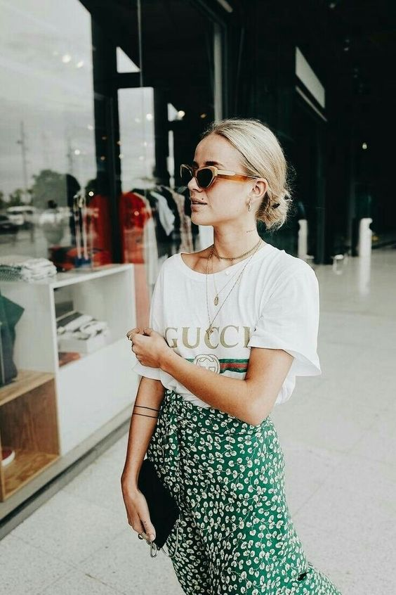 a Gucci tee, a green floral print midi and a mall clutch for a relaxed look