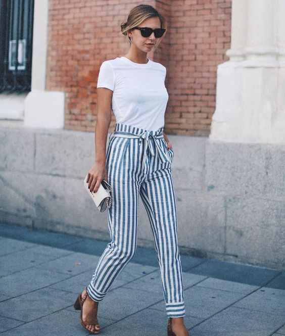 a white tee, high waist striped pants, tan shoes and a clutch