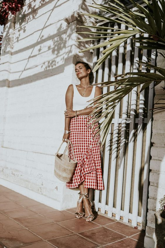 a white top, a red gingham asymmetrical midi skirt, strappy heels and a straw bag